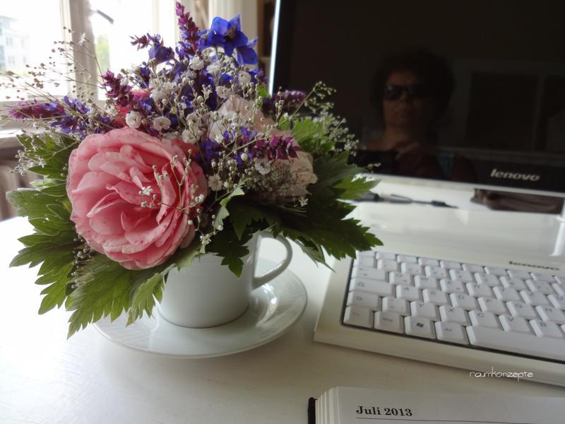 Arbeitsplatz mit Blumenstrauss in einer Teetasse