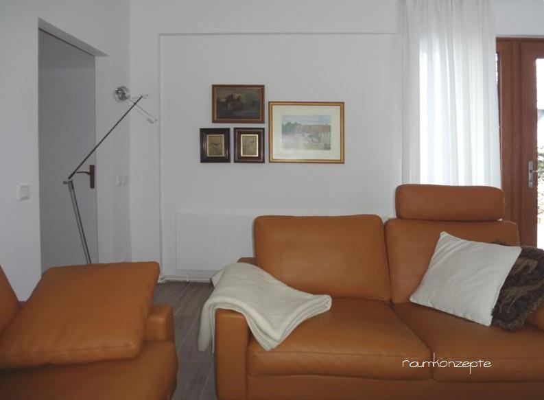 Wohnzimmer Sofa an Laengswand nach Umgestaltung in hellen Farben