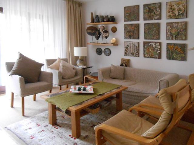 sandfabenes Sofa mit strukturierter Bilderanordnung nach Umgestaltung