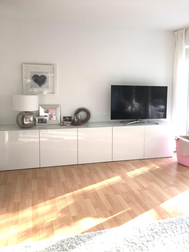 Wohnzimmer TV Umgebung nach Umgestaltung mit TV auf durchgehendem weissen Sideboard