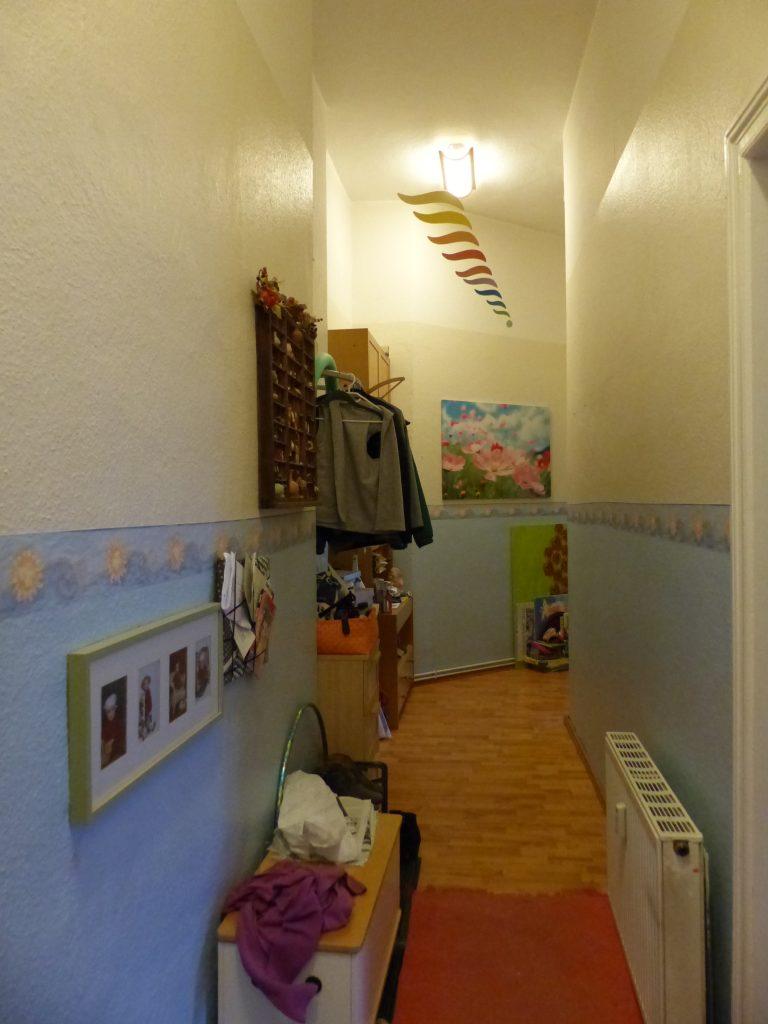 Flur Blick 6 vorher mit Garderobe, Heizkoerper und Waenden in hellblau und beige