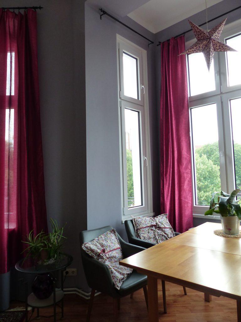 Wohnzimmer Blick 1 nachher mit Esstisch, grauer Wand und pinkfarbenen Vorhängen