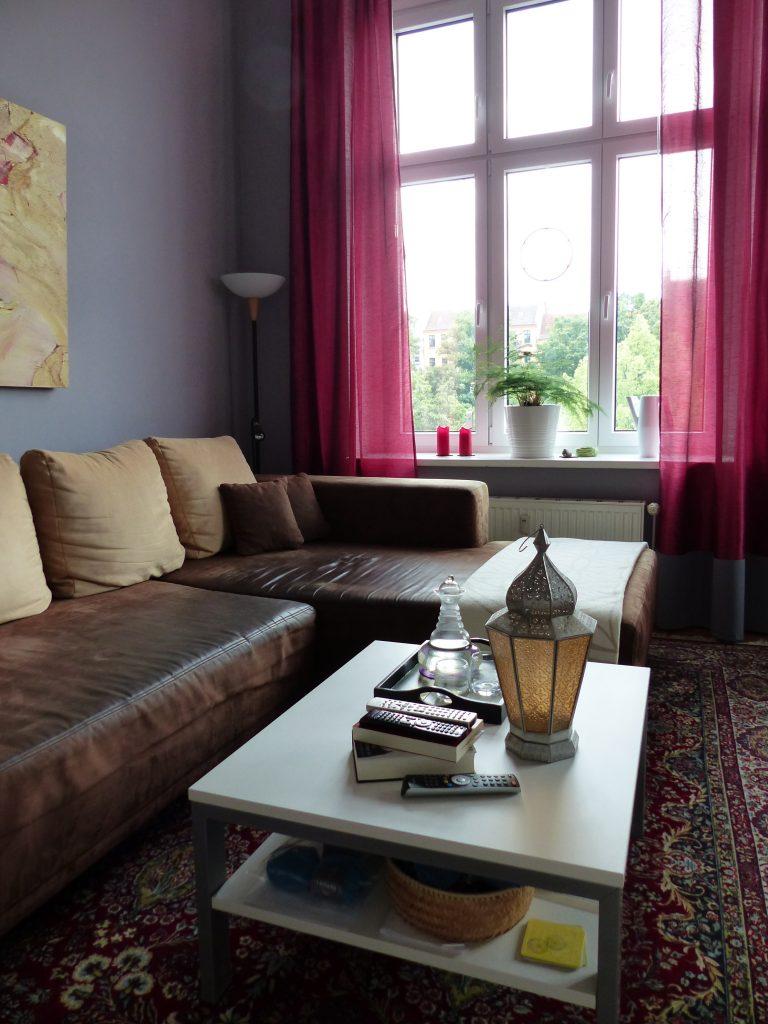 Wohnzimmer Blick 2 nachher mit Ecksofa, Couchtisch, grauer Wand und pinkfarbenen Vorhaengen