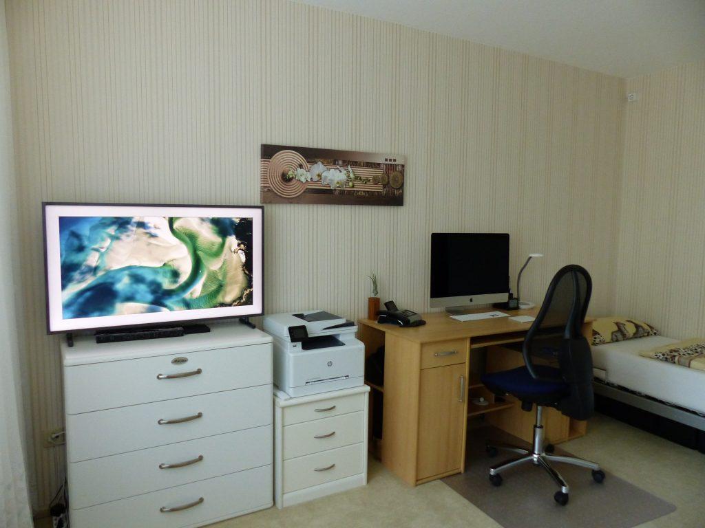 Arbeits-Schlafraum Blick 1 vorher mit Bett, Arbeitsplatz, Wandbild, Drucker und TV