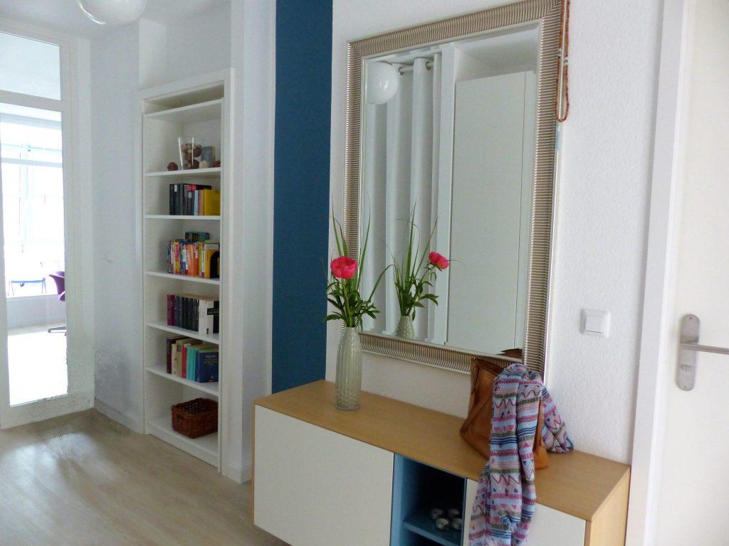 Flur Blick 1 nachher mit Wohnzimmertuer, Buecherregal in Tuer, blauem Wandteil, Sideboard und Spiegel