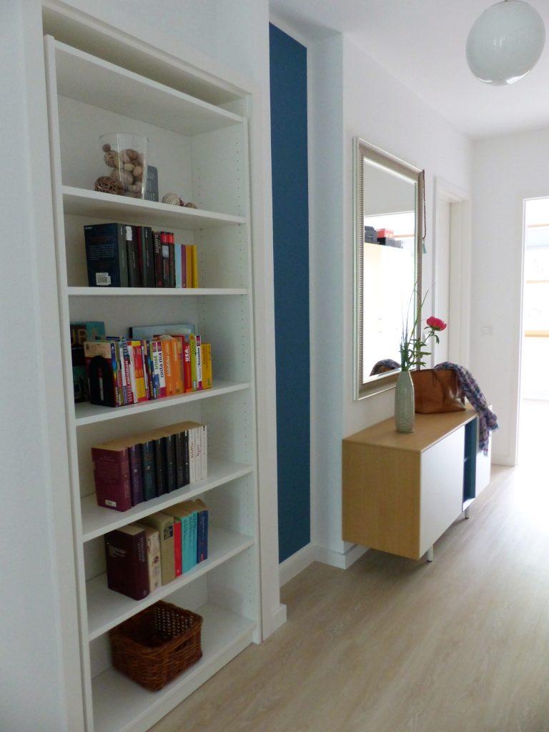 Flur Blick 3 nachher mit Buecherregal in Tuer, blauem Wandteil, Sideboard, Spiegel und Schlafzimmertuer