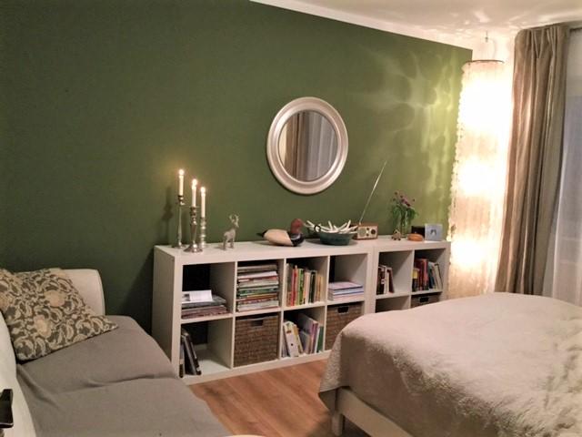 Grünes Schlafzimmer Blick 2 nachher mit moosgrüner Wand, Regal, Spiegel, Sofa, Bett, Ecklampe