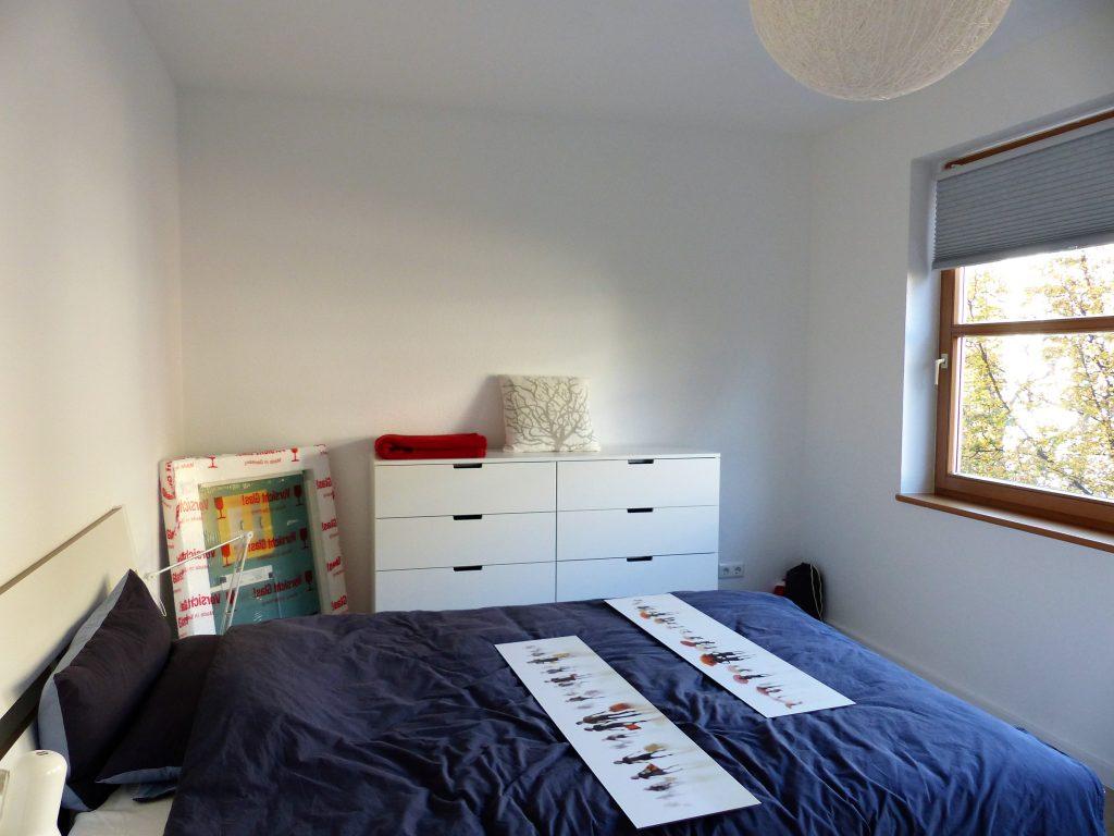 Schlafzimmer Blick 14 vorher mit Bett, blauem Bettzeug und Schubladenelement