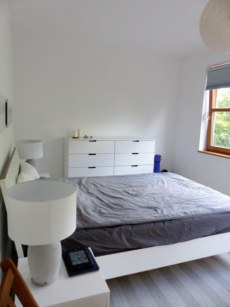 Schlafzimmer Blick 14 nachher mit Bett, grauem Bettzeug und Schubladenelement