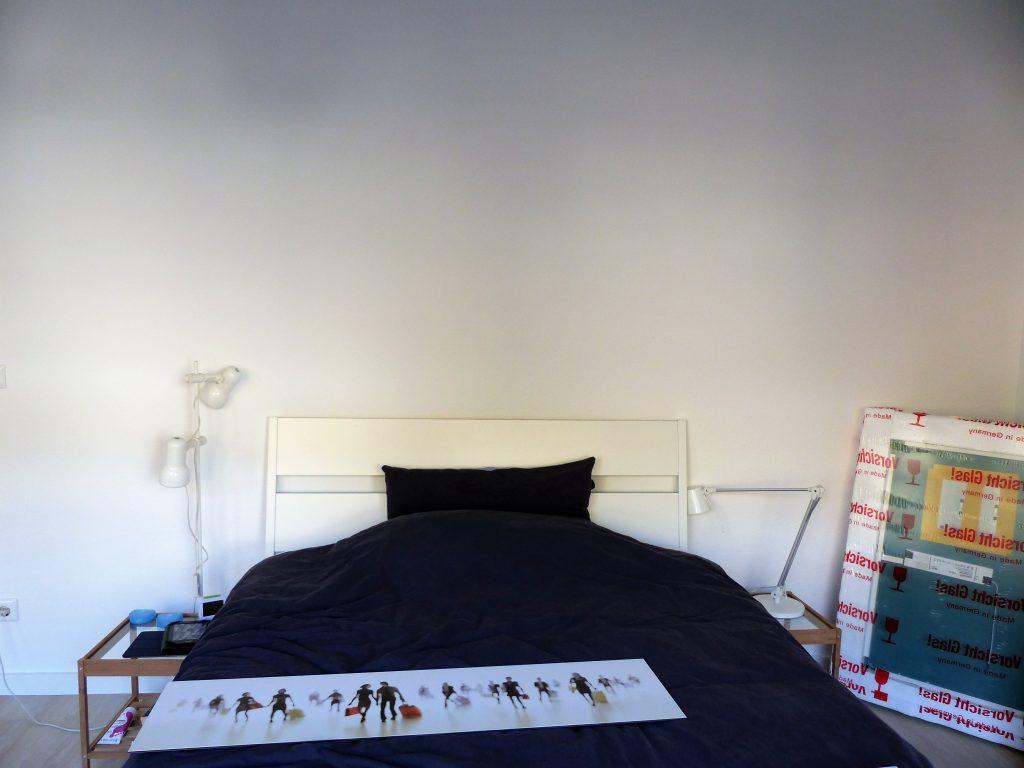 Schlafzimmer Blick 15 vorher mit Bett, blauem Bettzeug, Glastischen und weissen Lampen