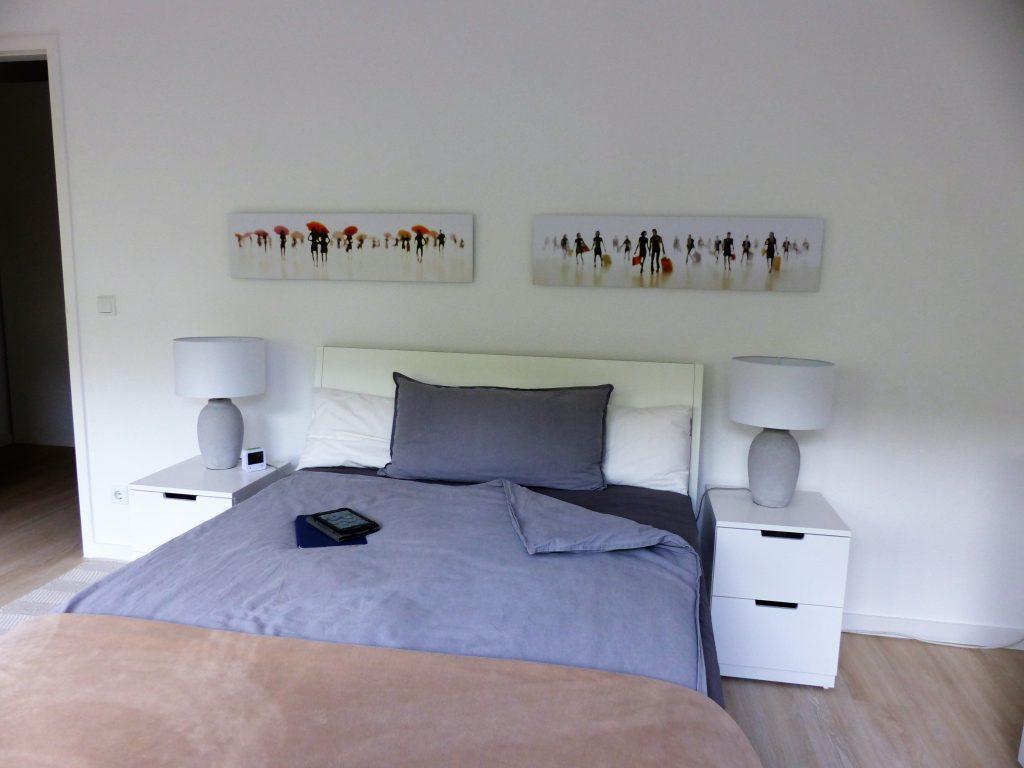 Schlafzimmer Blick 15 nachher mit Bett, grauem Bettzeug, weissen Nachttischen, grauen Lampen und Wandbildern