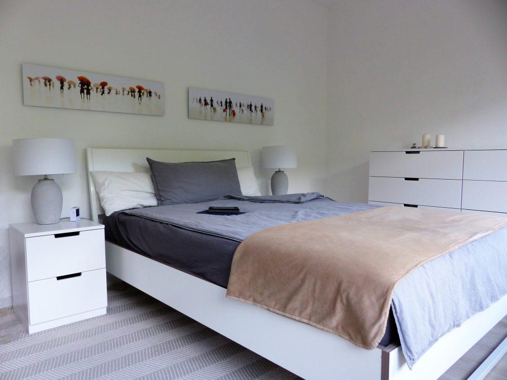 Schlafzimmer Blick 15 nachher mit Bett, grauem Bettzeug, weissen Nachttischen, grauen Lampen, Wandbildern und Schubladenelement