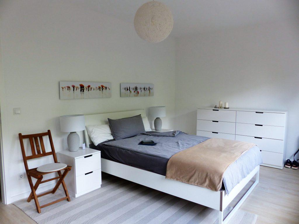Schlafzimmer Blick 15 nachher mit Stuhl, Bett, Nachttischen, Lampen, Wandbildern und Schubladenelement