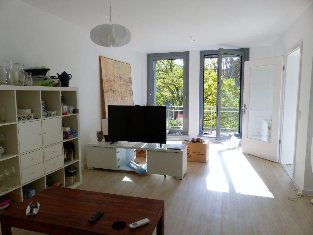 Wohnbereich Blick 5 vorher mit Couchtisch, Regal, TV und Balkonfenster