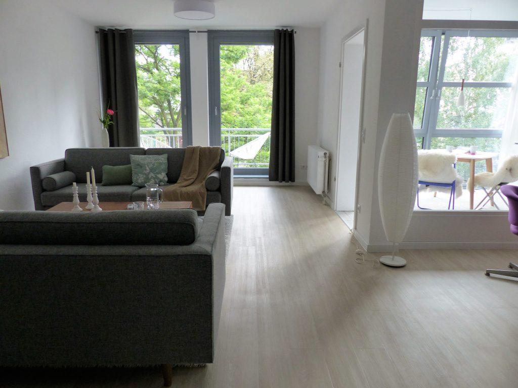 Wohnbereich Blick 5 nachher mit Zweisitzer, Couchtisch, Balkonfenster und Arbeitsraumabtrennung