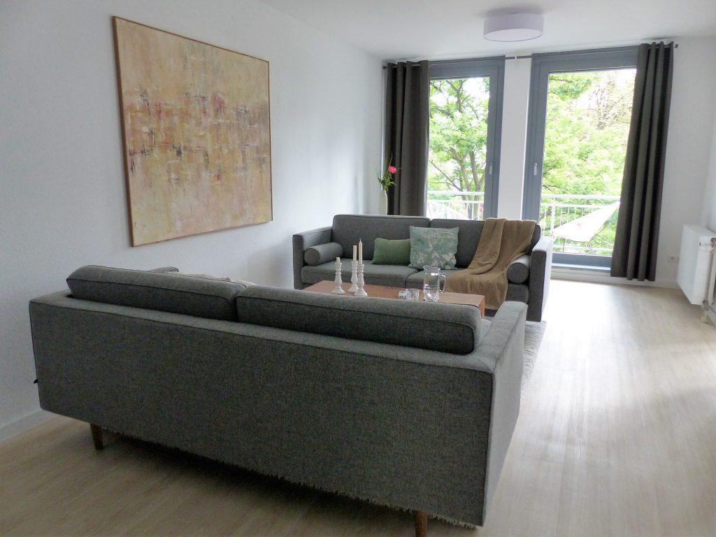 Wohnbereich Blick 5 nachher mit Zweisitzer, Couchtisch, Wandbild, Balkonfenster und Heizkoerper