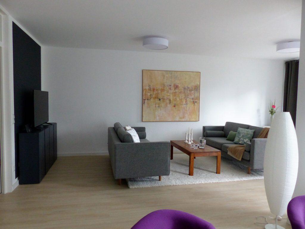 Wohnbereich Blick 7 nachher mit TV-Sideboard, Zweisitzer, Couchtisch, Wandbild, Teppich und Stehlampe