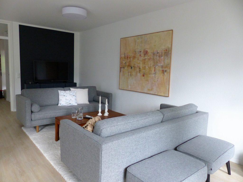 Wohnbereich Blick 9 vorher mit TV-Sideboard, Zweisitzer, Couchtisch, Wandbild und Polsterhocker