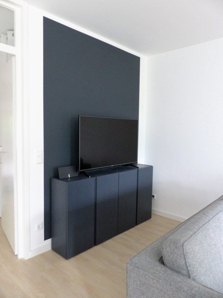Wohnbereich Blick 10 nachher mit schwarzem TV-Sideboard vor schwarzer Wand