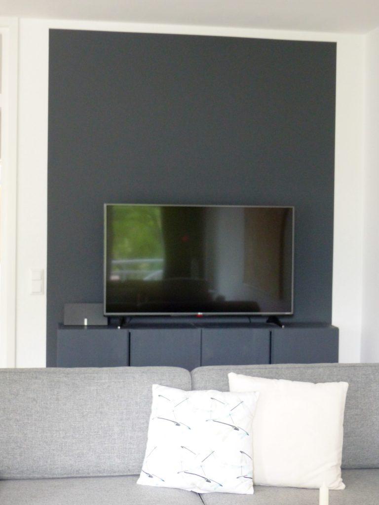 Wohnbereich Blick 10 nachher mit Zweisitzer und schwarzem TV-Sideboard vor schwarzer Wand