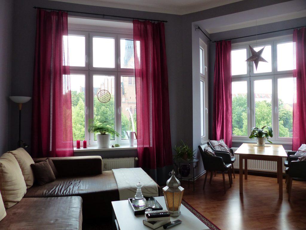 Wohnzimmer Blick 1 nachher mit Esstisch, Ecksofa und pinkfarbenen Vorhaengen