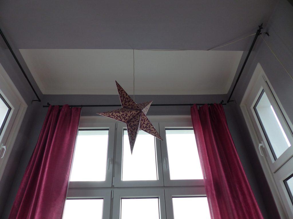 Wohnzimmer Blick 1 nachher mit weisser Decke, Sternlampe und pinkfarbenen Vorhaengen