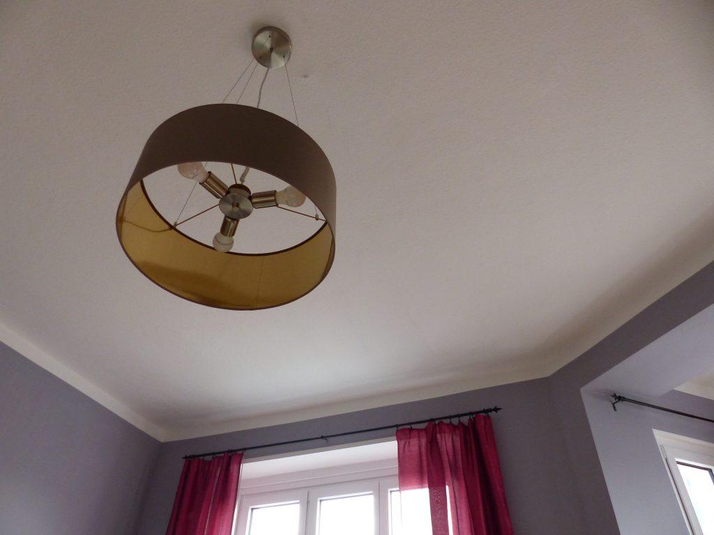 Wohnzimmer Blick 1 nachher mit weisser Decke, Deckenlampe und pinkfarbenen Vorhaengen