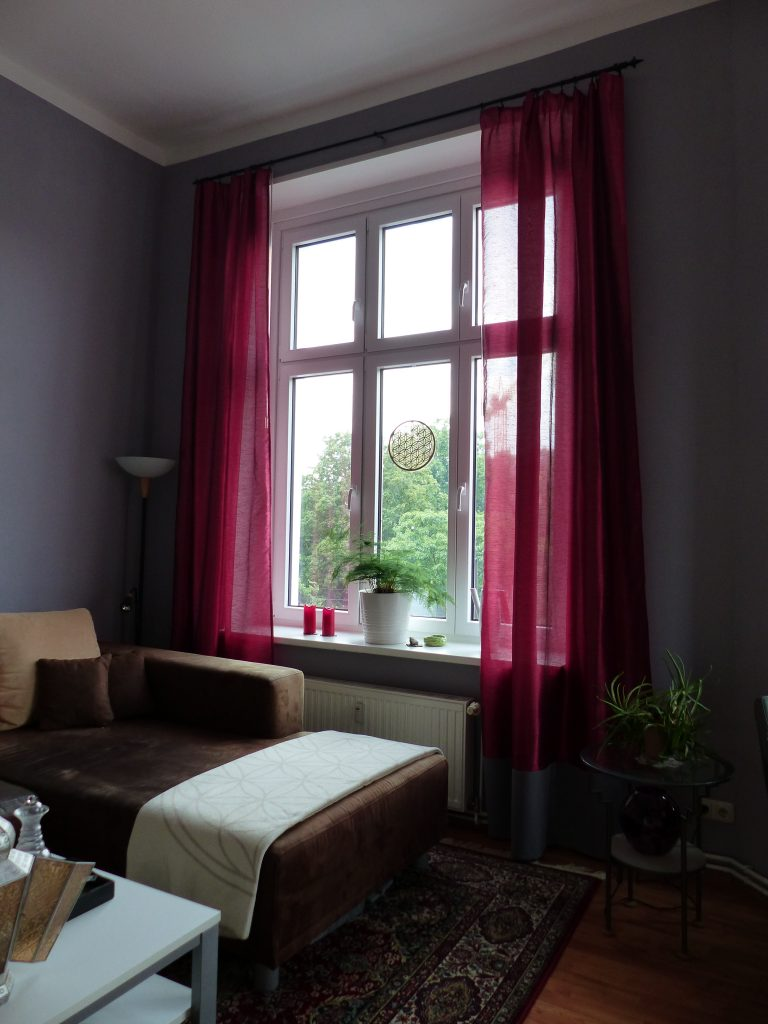 Wohnzimmer Blick 2 nachher mit Ecksofa, Stehlampe, grauer Wand und pinkfarbenen Vorhaengen