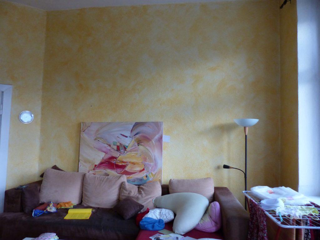 Wohnzimmer Blick 5 vorher mit Ecksofa und Waeschestaender vor gelber Wand