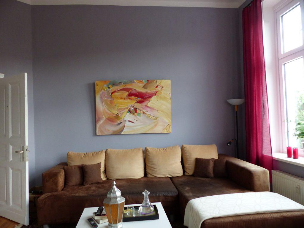 Wohnzimmer Blick 5 nachher mit Couchtisch, Ecksofa und Wandbild vor grauer Wand