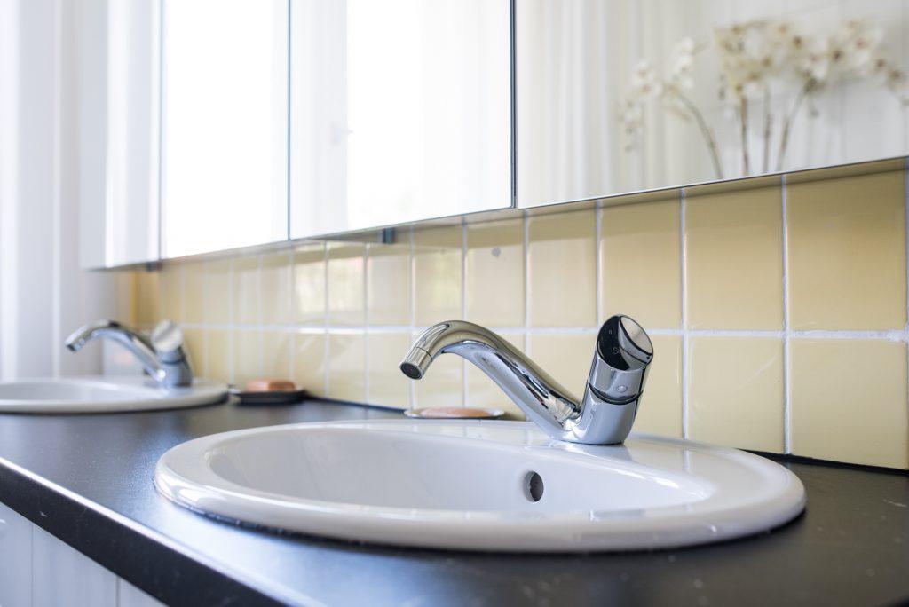 Altbaubad im neuen Style mit zwei geschwungenen Wasserhähnen an zwei Waschbecken
