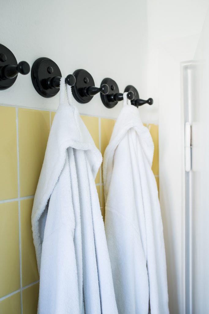 Altbaubad im neuen Style mit weißen Bademänteln an schwarzen Garderobenhaken