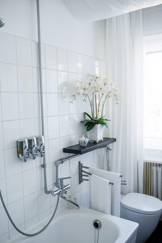 Altbaubad im neuen Style mit silberfarbenen Wasserleitungen vor weißen Fliesen