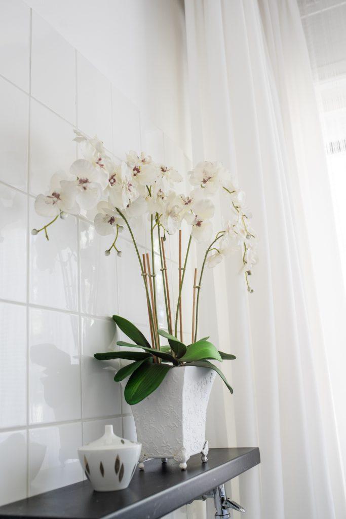 Altbaubad im neuen Style mit weißen Orchideen auf schwarzer Ablage