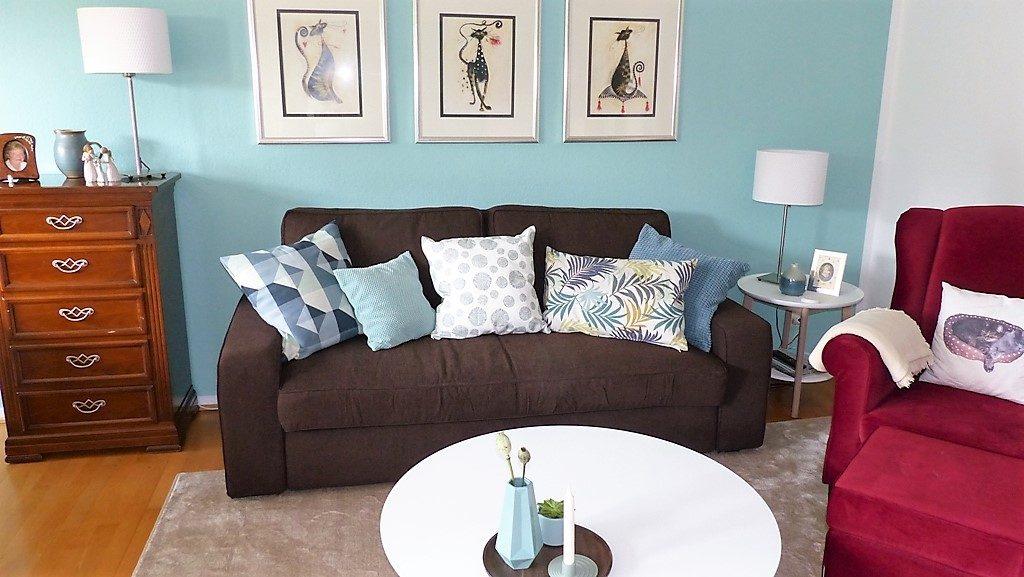 Internet-Wohnzimmer-nachher mit braunem Sofa, drei Bildern vor grüner Wand