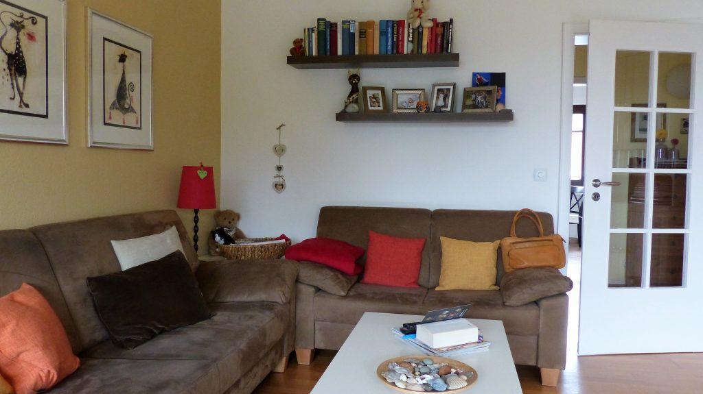 Internet-Wohnzimmer-vorher mit zwei eng stehenden grauen Sofas, Bilder und Wandregalen