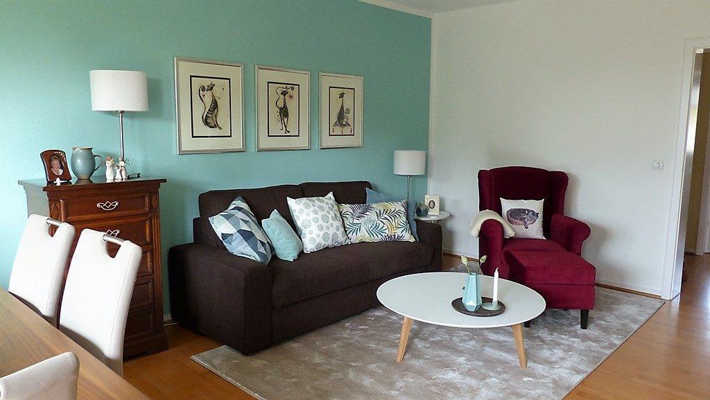Internet-Wohnzimmer-nachher mit braunem Sofa und rotem Sessel vor weißer Wand