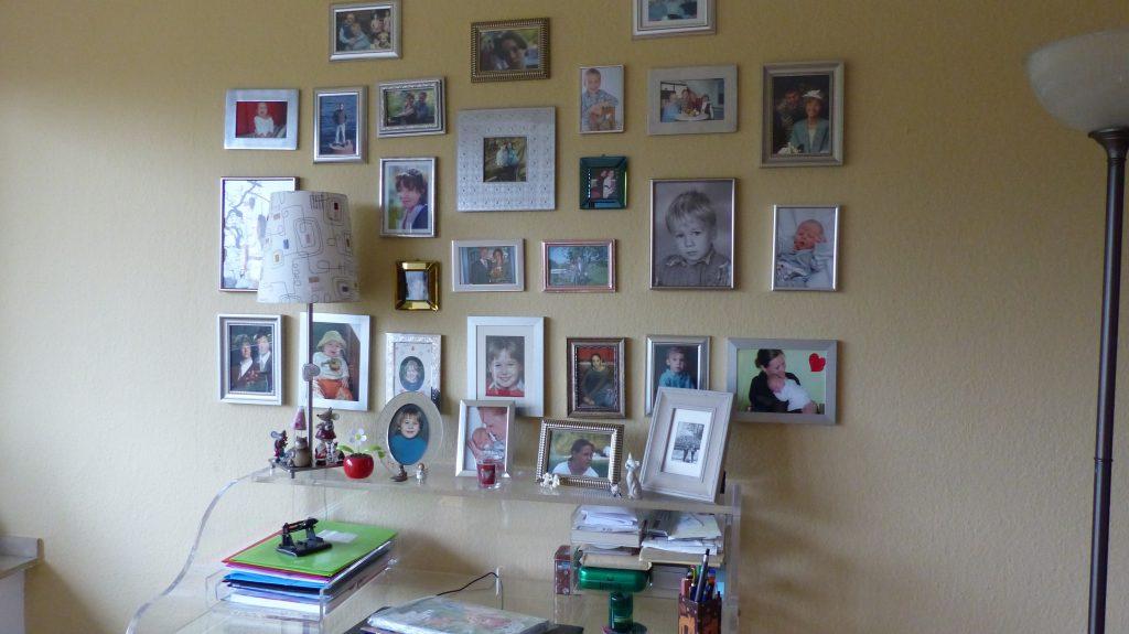 Internet-Wohnzimmer-vorher mit vielen gerahmten Fotos auf brauner Wand