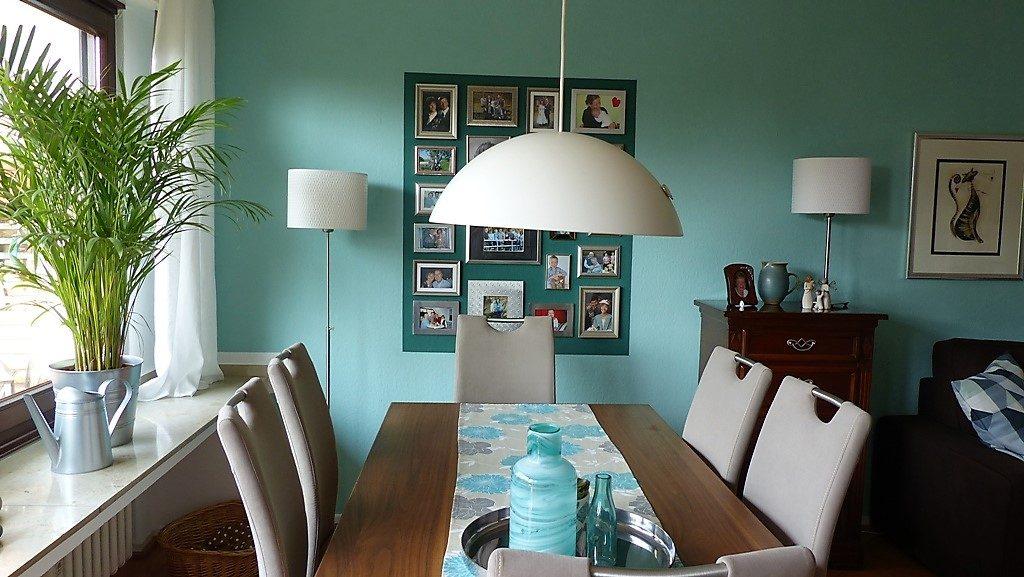 Internet-Wohnzimmer-nachher mit diversen Bildern vor dunkelgrünem Farbspiegel an der Wand
