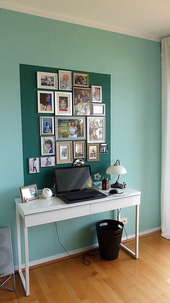 Internet-Wohnzimmer-nachher mit weißem Schreibtisch und diversen Bildern vor dunkelgrünem Farbspiegel an der Wand