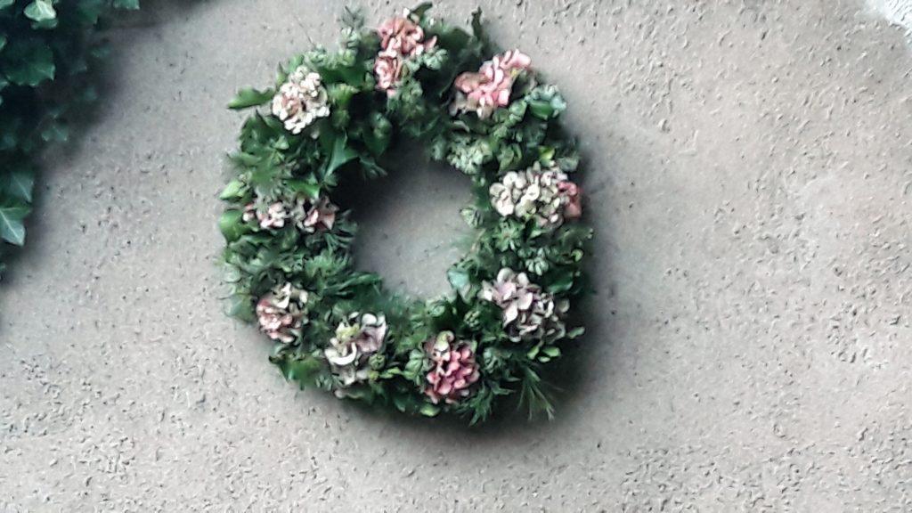Kranz aus Hortensien, Tanne und Efeu vor grauer Gartenmauer