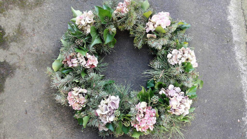 Kranz aus Hortensien, Tanne und Efeu mit vielen getrockneten Blüten vor grauer Gartenmauer