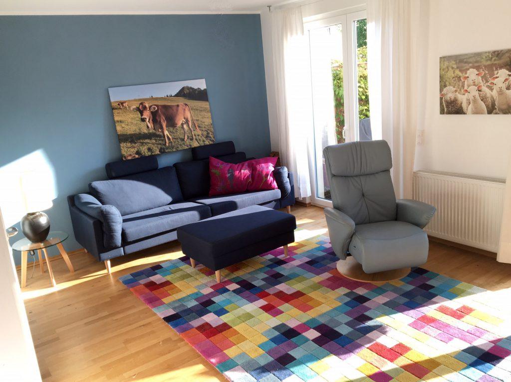 angezogenes Wohnzimmer nach Umgestaltung mit blauem Sofa an der Wand