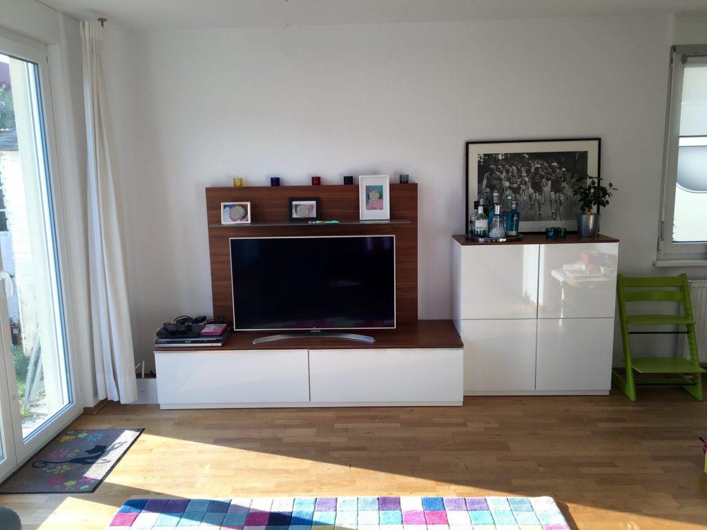angezogenes Wohnzimmer nach Umgestaltung mit weißen TV-Möbeln