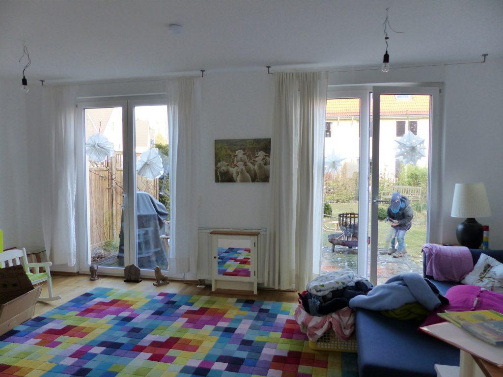 angezogenes Wohnzimmer vor Umgestaltung mit Polsterhocken vor Terrassentür