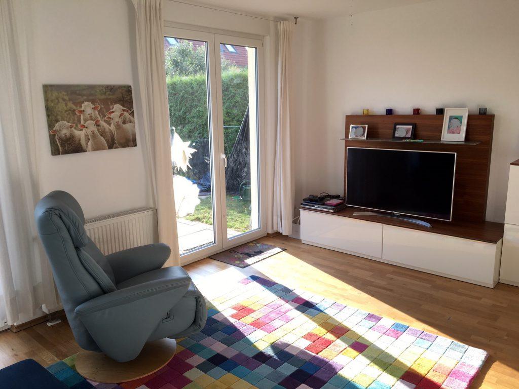 angezogenes Wohnzimmer nach Umgestaltung mit blauem Sessel und freiem Durchgang zur Terrasse
