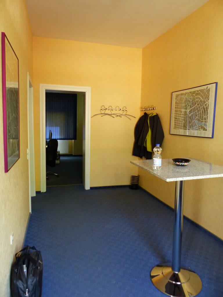 Schulungsraum vor Umgestaltung mit gelber Wand vor Stehtisch im Eingangsbereich