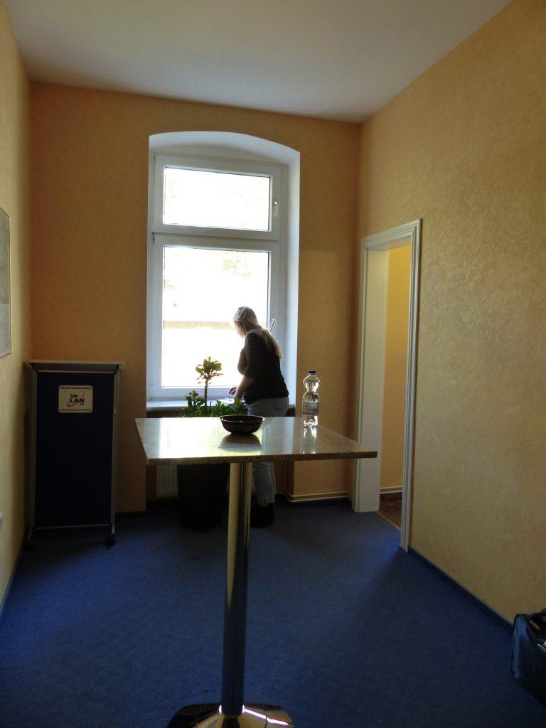 Schulungsraum vor Umgestaltung mit Fenster in gelber Wand und Stehtisch auf blauem Teppich