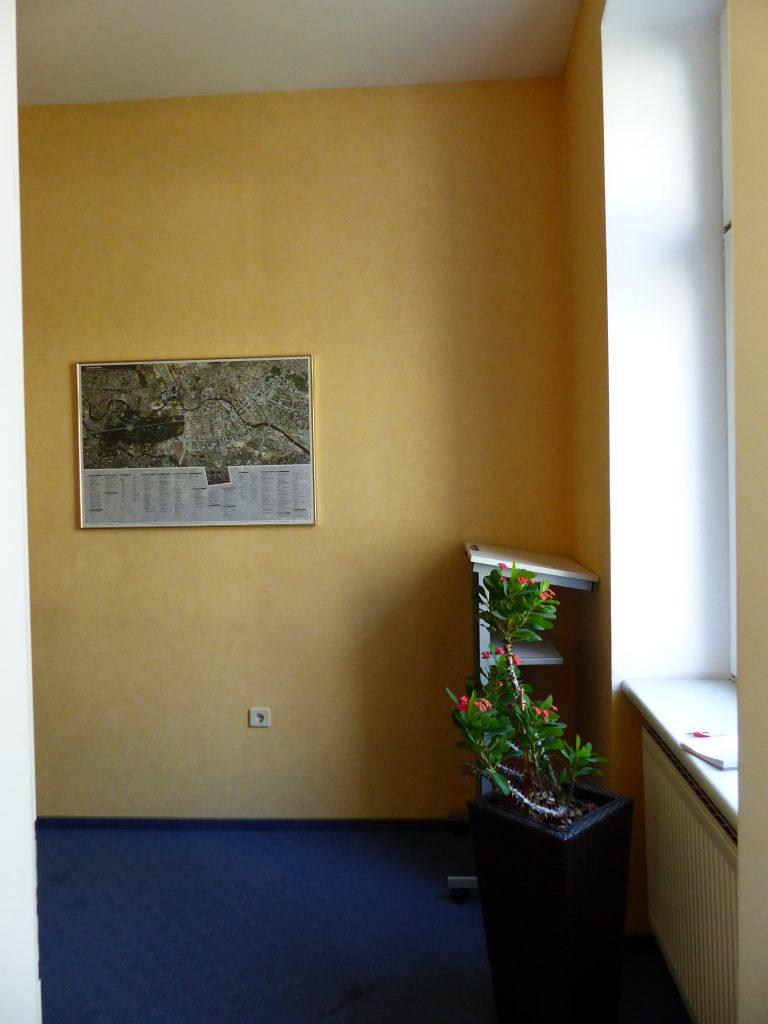 Schulungsraum vor Umgestaltung mit gelber Wand und weißer Fensternische