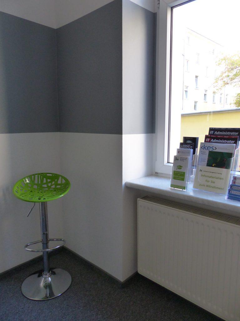 Schulungsraum nach Umgestaltung mit weißer Wand und grauem Farbstreifen bis in die Fensternische und grünem Stehhocker